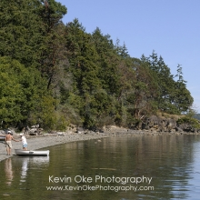 People getting out of a dinghy at the beach in Princess Bay, Portland Island, British Columbia, Canada