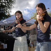 Two violin players performing at the Salt Spring Island Saturday Market located in Ganges, Ganges, Salt Spring Island, British Columbia