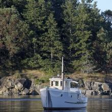 Old wooden fishing boat at anchor in Princess Bay, Portland Island, British Columbia, Canada