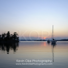 Boats anchored on a calm ocean at sunset, Wallace Island, Gulf Islands, British Columbia, Canada
